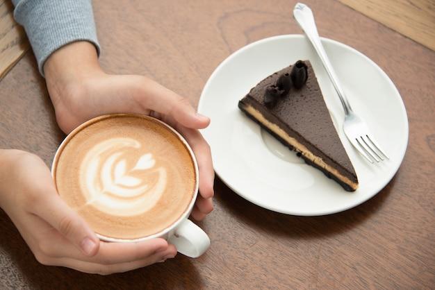 Frau trinkt cappuccino und isst kuchen