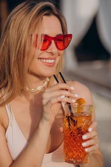 Frau trinkt cocktail am pool