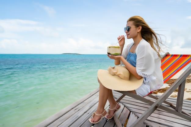 Frau trinkt ein kokosnusswasser auf bequemen stuhl am strand.