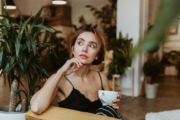 Frau trinkt einen kaffee in ihrem wohnzimmer