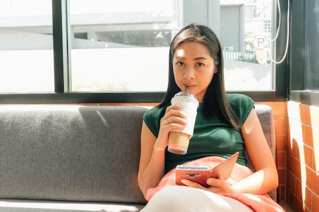 Frau trinkt gefrorenen kaffee und benutzt ihren smartphone auf dem sofa in der ecke des cafés