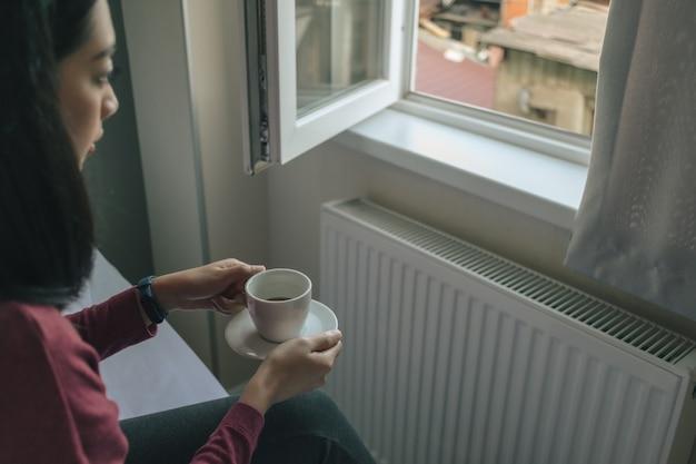 Frau trinkt heißen kaffee und schaut zum fenster in ihrer wohnung.