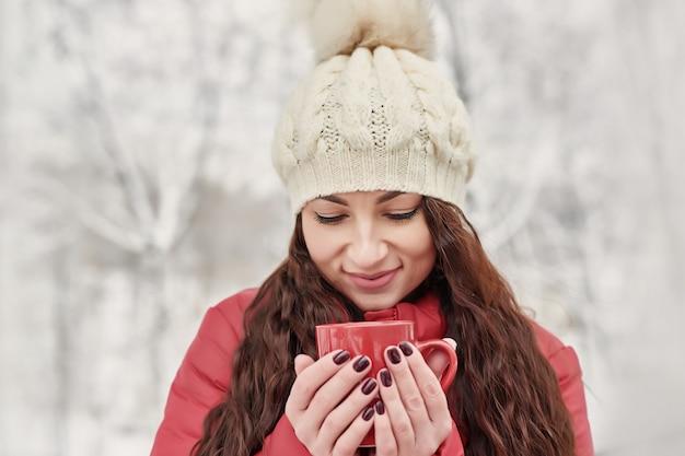 Frau trinkt heißen tee oder kaffee von der schale an gemütlichem snowy-haus-garten am wintermorgen. schönheit, die draußen winter mit becher des warmen getränks genießt. weihnachtsferien. gemütlicher winter-lifestyle.