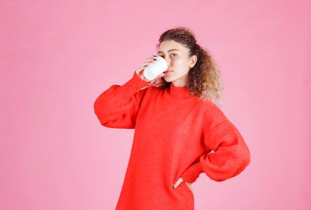 Frau trinkt kaffee aus einem einwegbecher.