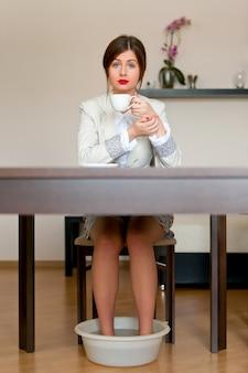Frau trinkt kaffee mit nassen füßen