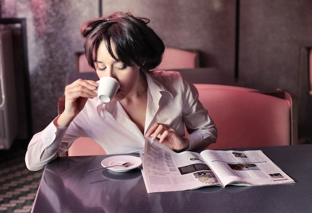Frau trinkt kaffee und liest eine zeitschrift