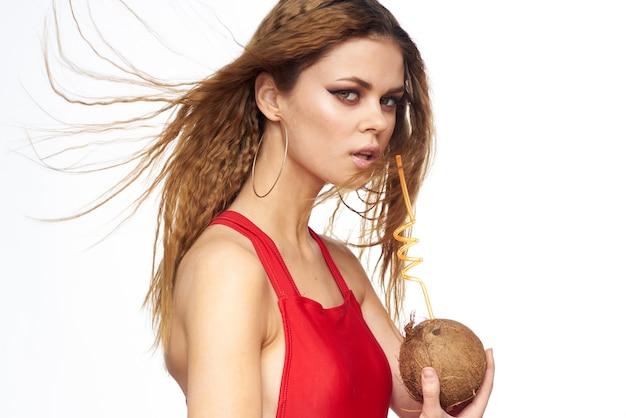 Frau trinkt kokosnusscocktail durch eine rote wand des roten t-shirts des strohlebens.