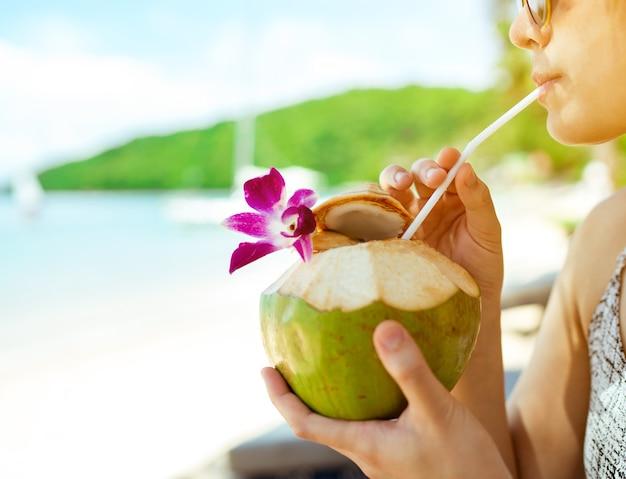 Frau trinkt kokoswasser auf bequemen stuhl am strand