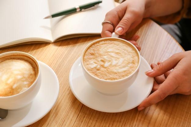 Frau trinkt leckeren kaffee am tisch im café