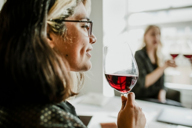 Frau trinkt mit freunden ein glas rotwein