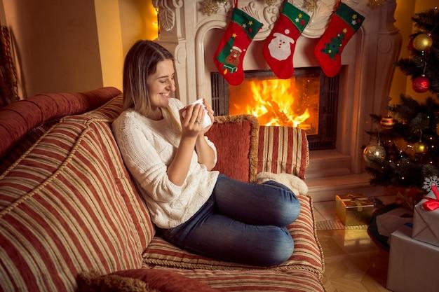 Frau trinkt tee am brennenden kamin zu weihnachten