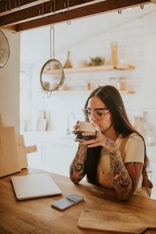 Frau trinkt tee, um sich nach der arbeit zu entspannen, während wfh