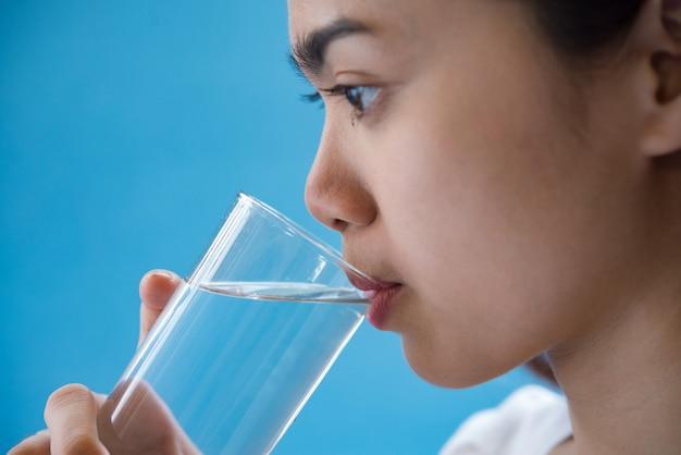 Frau trinkt wasser nach der einnahme eines arzneimittels