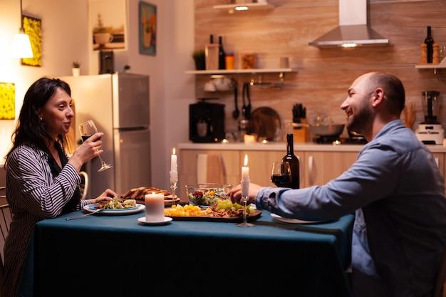 Frau trinkt wein und isst mit ehemann zu abend und genießt leckeres essen. glückliches paar spricht, sitzt am tisch im esszimmer, genießt das essen, feiert ihren jahrestag mit romantischer zeit.