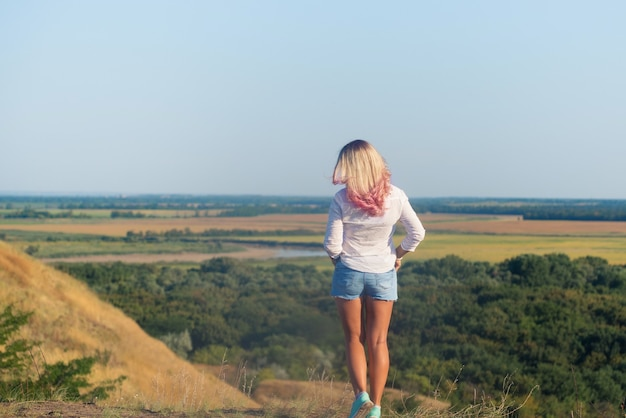 Frau trug weißes hemd und blaue shorts mit langen blonden rosa haaren, die auf dem berg standen