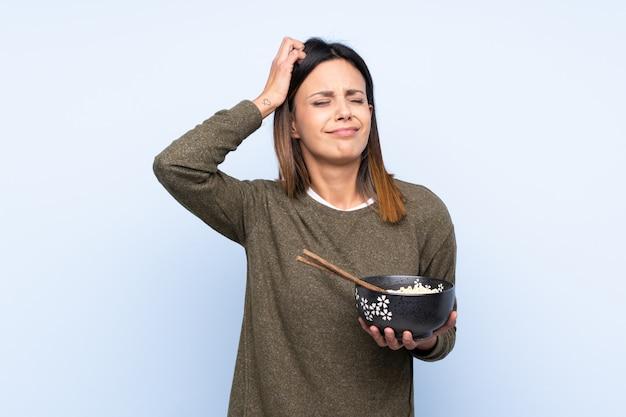 Frau über der blauen wand, die zweifel hat und mit verwirren gesichtsausdruck beim halten einer schüssel nudeln mit essstäbchen