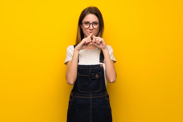 Frau über der gelben wand, die ein zeichen der ruhegeste zeigt