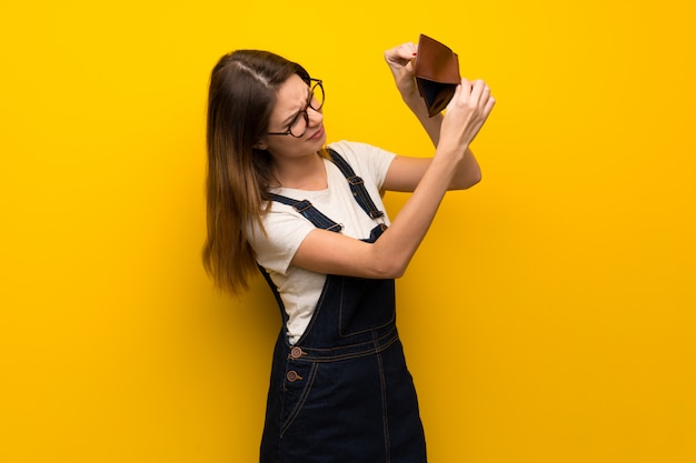 Frau über der gelben wand, die eine geldbörse hält