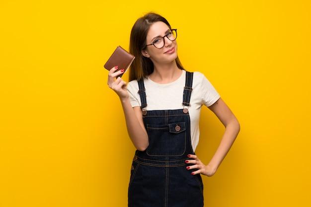 Frau über der gelben wand, die eine mappe anhält