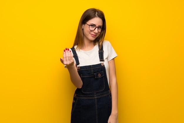 Frau über der gelben wand, die einlädt, mit der hand zu kommen. glücklich, dass du gekommen bist