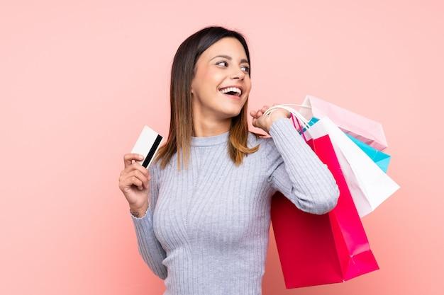 Frau über der rosa wand, die einkaufstaschen und eine kreditkarte hält