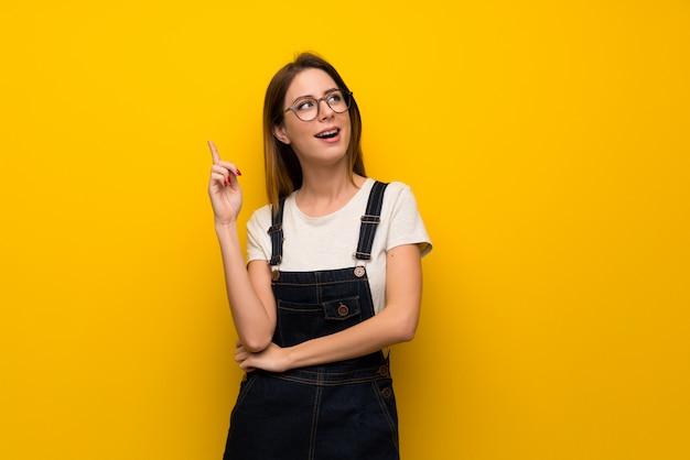 Frau über gelber wand eine idee denkend, die oben den finger zeigt