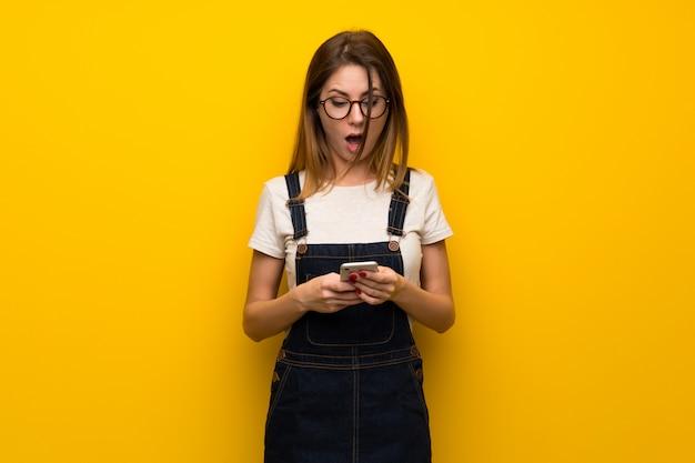 Frau über gelber wand überrascht und eine mitteilung sendend