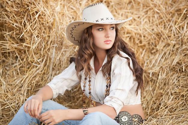 Frau über heu. junge frau in der cowboyartkleidung