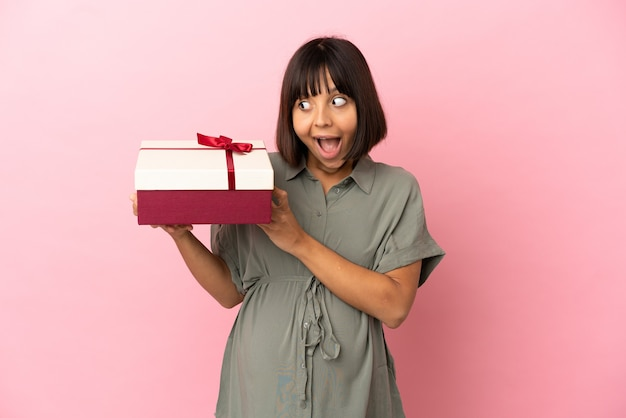 Frau über isoliertem hintergrund schwanger und hält ein geschenk mit überraschtem ausdruck
