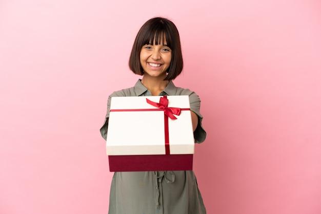 Frau über isoliertem hintergrund schwanger und hält ein geschenk