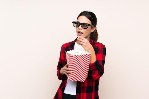 Frau über wand mit 3d-brille und hält einen großen eimer popcorn, während seite schauen