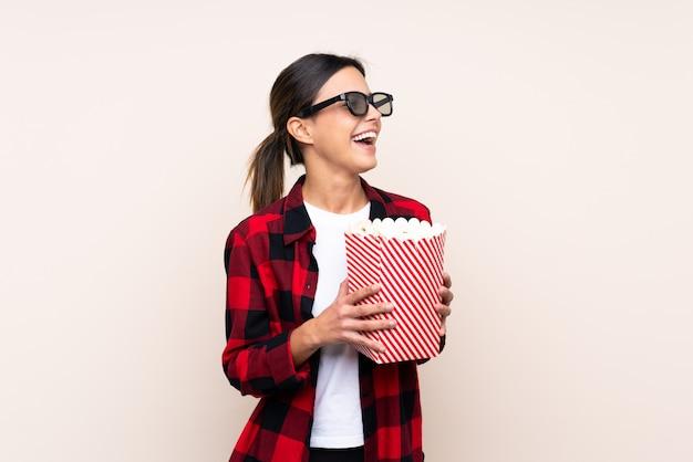 Frau über wand mit 3d-brille und hält einen großen eimer popcorn