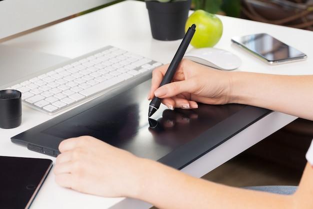 Frau übergibt den grafikdesigner, der an digitaler tablette arbeitet