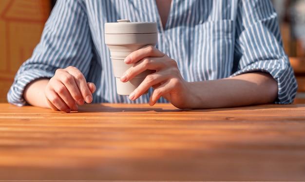 Frau übergibt nahaufnahme mit wiederverwendbarer öko-kaffeetasse aus silikon zum mitnehmen in den händen über holztisch