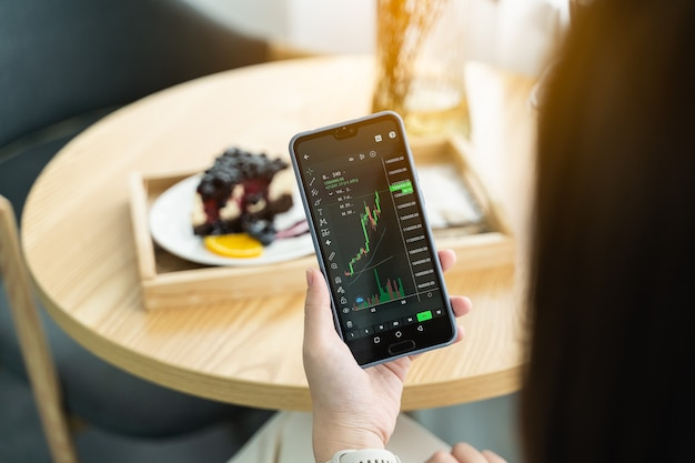 Frau überprüft bitcoin-preisdiagramm auf digitalem austausch auf smartphone im café