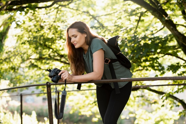 Frau überprüft die fotos, die sie mit ihrer digitalkamera aufgenommen hat