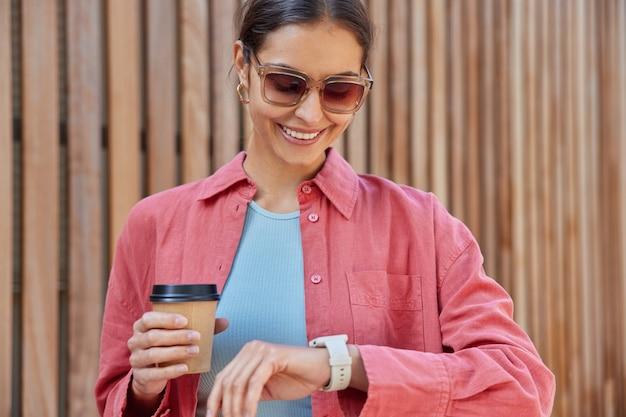Frau überprüft die zeit auf der uhr hält kaffee zum mitnehmen genießt koffeingetränk trägt eine sonnenbrille rosa hemd wird sich mit einem freund treffen lächelt angenehm