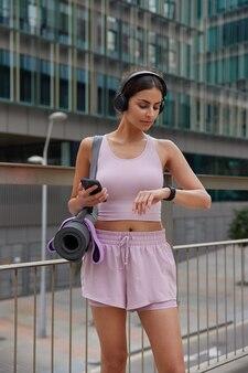 Frau überprüft fitness-tracker-daten oder körpervitalitäten während des trainings hält modernes smartphone mit heruntergeladenen sportanwendungs-posen in urbaner umgebung bereitet sich auf yoga-praxis vor