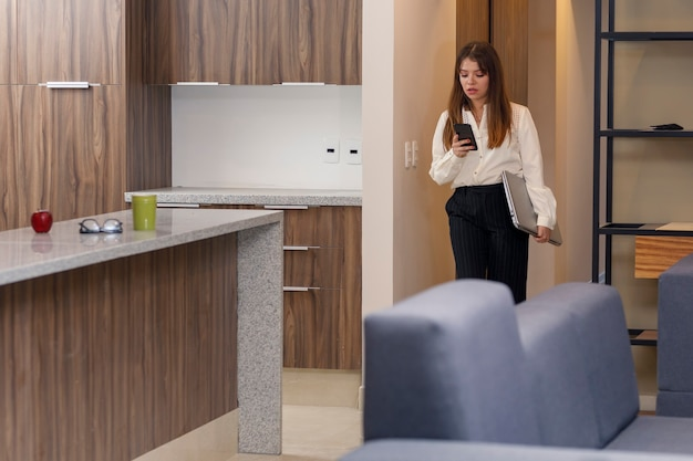 Frau überprüft ihr handy, während sie das haus verlässt, um zur arbeit zu gehen frau, die das haus verlässt, um zu arbeiten