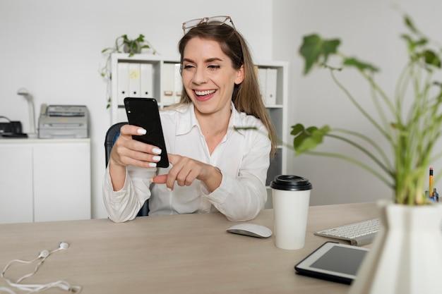 Frau überprüft ihr smartphone bei der arbeit