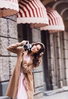 Frau überprüft ihre retro- kamera, die auf der straße steht