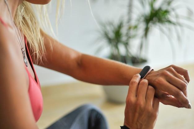 Frau überprüft ihre trainingszeit auf smartwatch zu hause