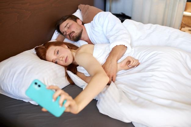 Frau überprüft sms und nachrichten am telefon, junges paar nach der nacht