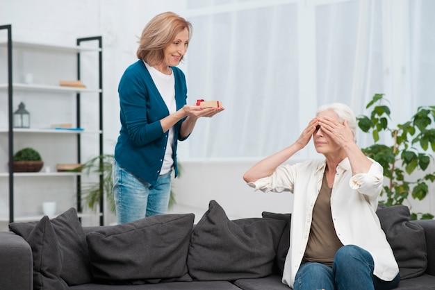 Frau überrascht ihre freundin mit einem geschenk