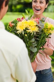 Frau überrascht, wie sie von ihrem freund mit blumen präsentiert wird