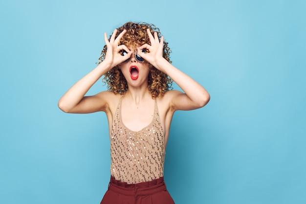Frau überraschungsgesten mit den händen nahe dem lockigen haargesicht-paillettenhemd