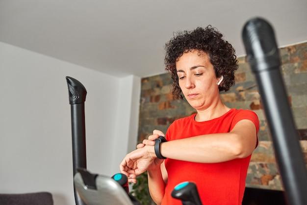 Frau überwacht das training auf ihrem smartband