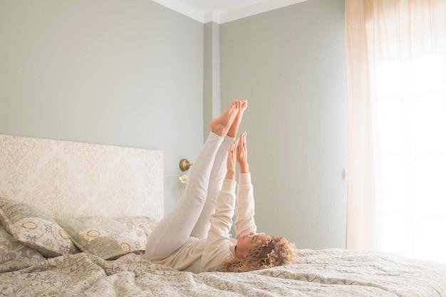 Frau übt einen aktiven lebensstil aus, der auf dem bett im schlafzimmer liegt