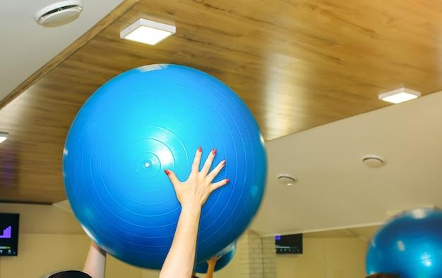 Frau übt mit blauen fitballs in den händen im fitnesscenter. gymnastikbälle im fitnessstudio für einen gesunden lebensstil.