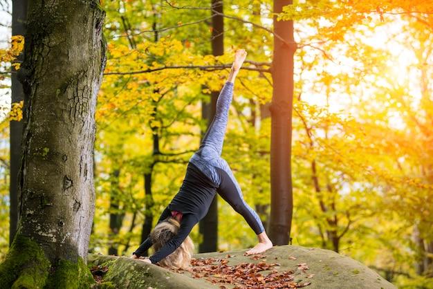 Frau übt yoga im herbstwald auf dem großen stein